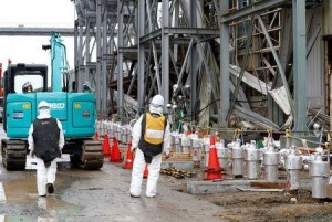 Workers wearing radiation protective gear stand outside of the No. 4 reactor building at TEPCO's tsunami-crippled Fukushima Daiichi nuclear power plant in Fukushima prefecture